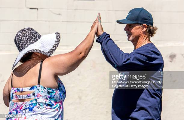 Kandy McGuire, left, of Rancho Cucamonga gives artist Wyland a high-five after viewing Wyland's recreation of the first of his 100 whaling walls on a...