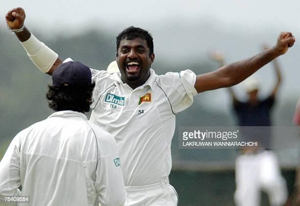 Sri Lankan cricketer Muttiah Muralitharan celebrates with teammate Kumar Sangakkara the dismissal of unseen Bangladeshi cricketer Syed Rasel after...