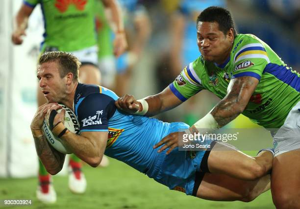 Kane Elgey of the Titans catches the ball to score a try past Joseph Leilua of the Raiders during the round one NRL match between the Gold Coast...