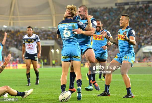 Kane Elgey of the Titans is congratulated by team mates after scoring a try during the round 25 NRL match between the Gold Coast Titans and the North...