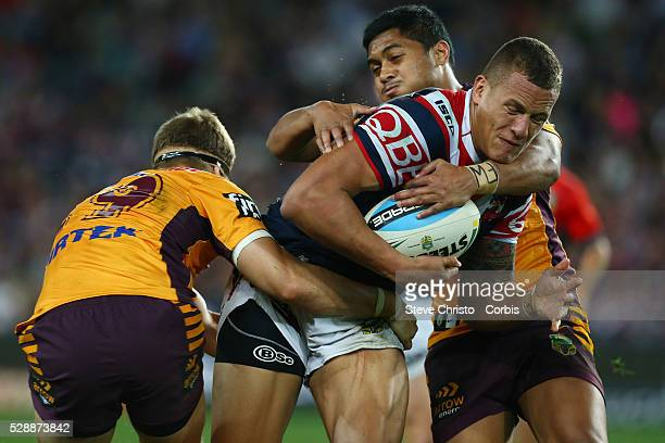 Kane Evans of the Roosters is tackled by Bronco's Dale Copley and Anthony Milford during the round 24 match between Sydney Roosters and Brisbane...