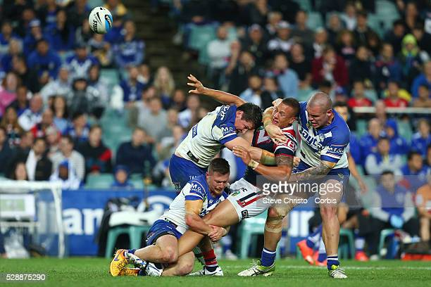 Kane Evans of the Roosters is tackled by the Bulldog's Josh Jackson, David Klemmer and Damien Cook during the Semi Final 1 match between the Sydney...