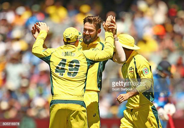 Kane Richardson of Australia is congratulated by his teammates after dismissing Rohit Sharma of India during game three of the One Day International...