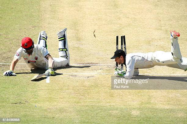 Kane Richardson of the Redbacks dives to into the crease as Sam Whiteman of the Warriors attempts a run-out during day three of the Sheffield Shield...