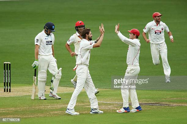 Kane Richardson of the SA Redbacks celebrates with teammates after he got the wicket of Daniel Hughes of the Blues during day one of the Sheffield...