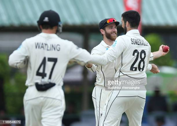 Kane Williamson of New Zealand celebrates with his team mate William Somerville after taking a catch to dismiss Lahiru Thirimanne of Sri Lanka during...