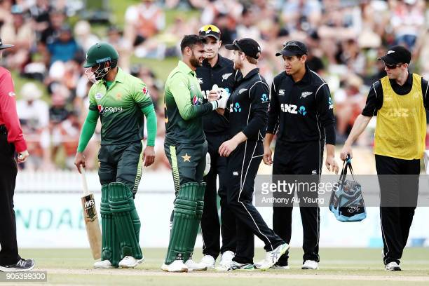 Kane Williamson of New Zealand checks on Shoaib Malik of Pakistan's well being after being hit on the head by a ball during game four of the One Day...