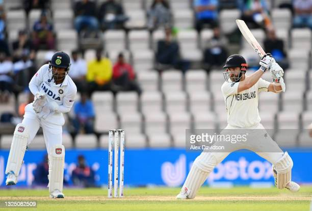 Kane Williamson of New Zealand hits runs watched on by Rishabh Pant of India during the Reserve Day of the ICC World Test Championship Final between...