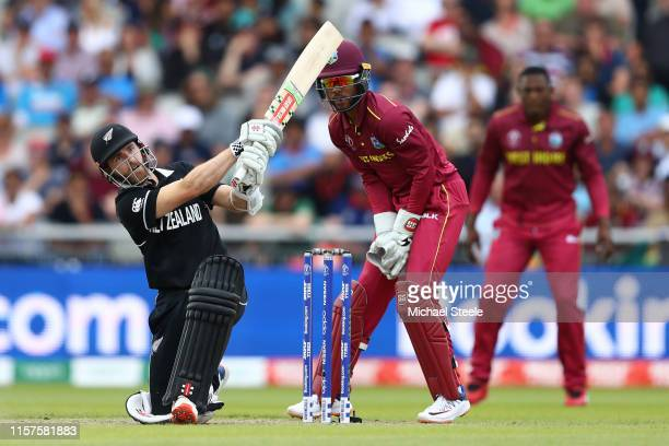 Kane Williamson of New Zealand hits to the mid wicket boundary as wicketkeeper Shai Hope looks on during the Group Stage match of the ICC Cricket...