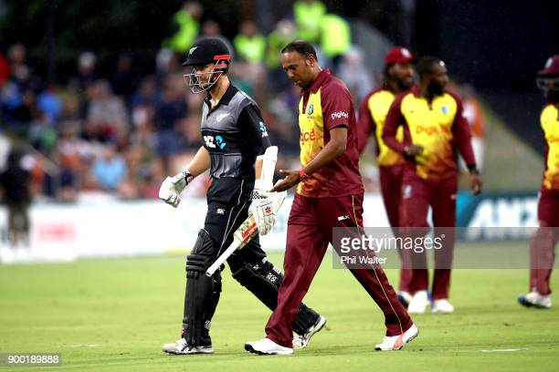 Kane Williamson of New Zealand leaves the field with Ashley Nurse of the West Indies as play is postponed due to rain during game two of the Twenty20...