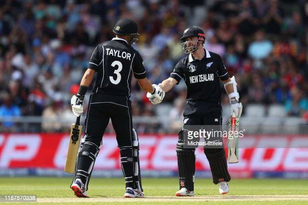 Kane Williamson of New Zealand shakes hands with Ross Taylor after reaching his half century during the Group Stage match of the ICC Cricket World...