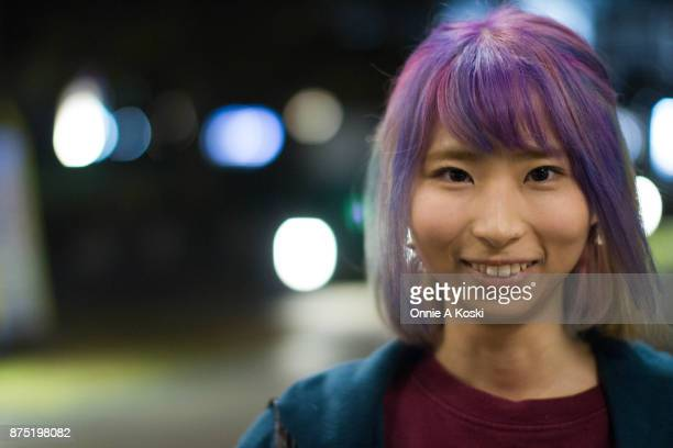Kaneko Hanano with purple pink and green hair wearing a blue coat a burgundy shirt with cat print Dr Martens leather black shoes Vivienne Westwood...