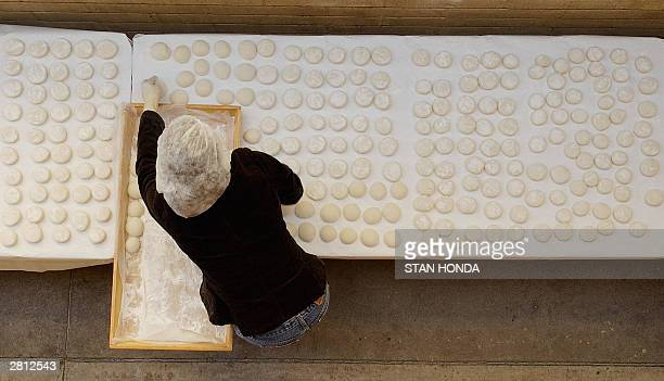 Kaneko Kuwada places Japanese rice cakes called mochi on a table to help them cool off 14 December at the Buddhist Temple in San Diego CA The...