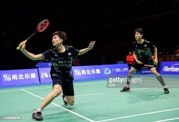 Kang Minhyuk and Kim Wonho of South Korea play a return against Hiroyuki Endo and Yuta Watanabe of Japan during their men's doubles semifinal match...