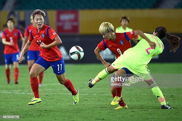 Kang Yumi of South Korea fights the ball with Emi Nakajima of Japan during their women's East Asian Cup football match at the Wuhan Sports Center...
