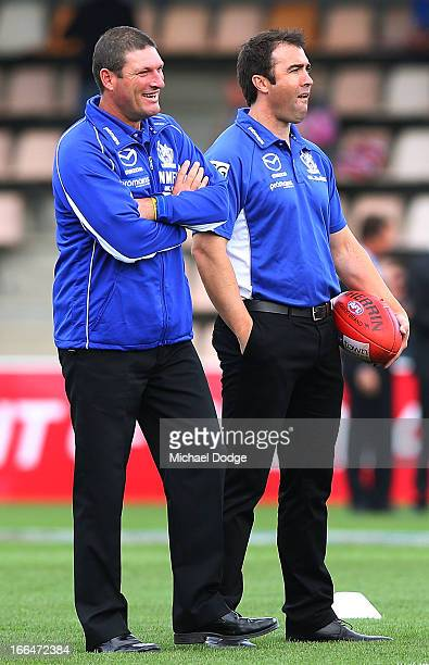 Kangaroos coach Brad Scott looks ahead with assistant coach Brett Allison during the round three AFL match between the North Melbourne Kangaroos and...