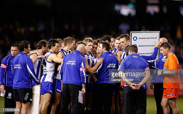 Kangaroos coach Brad Scott speaks with his players during the round 15 AFL match between the North Melbourne Kangaroos and the Richmond Tigers at...