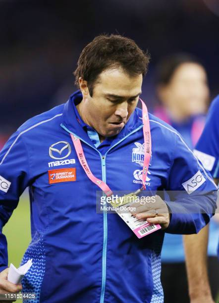 Kangaroos head coach Brad Scott checks his accreditation at quarter time during the round 10 AFL match between the Western Bulldogs and the North...