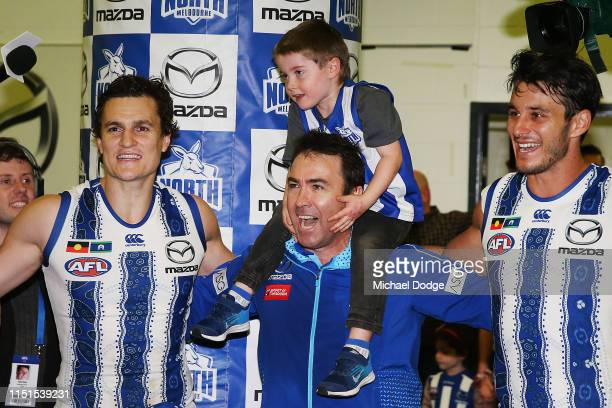 Kangaroos head coach Brad Scott sing the club song after winning with his sonand Robbie Tarrant of the Kangaroos and Scott Thompson during the round...