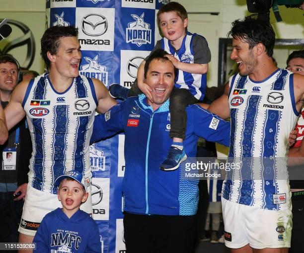 Kangaroos head coach Brad Scott sing the club song after winning with his son and Robbie Tarrant of the Kangaroos and Scott Thompson during the round...