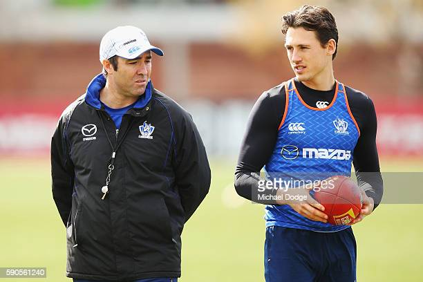 Kangaroos head coach Brad Scott speaks with Ben Jacobs during a North Melbourne Kangaroos AFL training session at Arden Street Ground on August 17,...