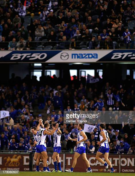 Kangaroos players celebrate a goal during the round 15 AFL match between the North Melbourne Kangaroos and the Richmond Tigers at Etihad Stadium on...