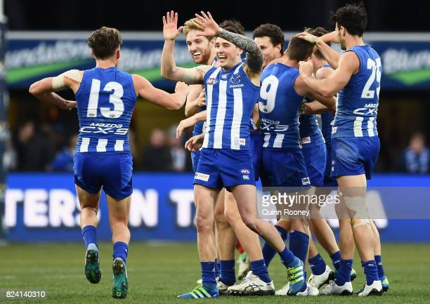 Kangaroos players celebrate winning the round 19 AFL match between the North Melbourne Kangaroos and the Melbourne Demons at Blundstone Arena on July...