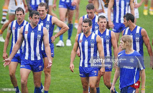 Kangaroos players walk off after the game was called off due to the rain during the AFL NAB Cup match between the North Melbourne Kangaroos and the...