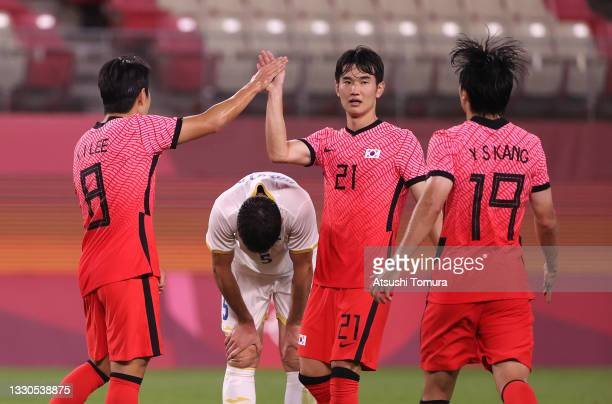 Kangin Lee of Team South Korea celebrates with teammate Jingyu Kim after scoring their side's fourth goal during the Men's First Round Group B match...
