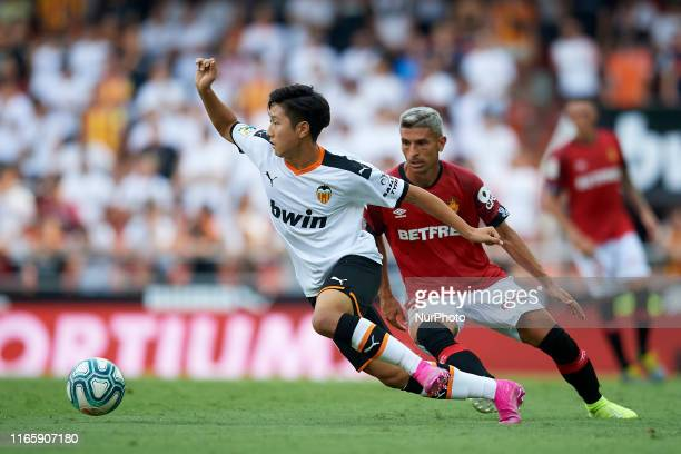 Kangin Lee of Valencia and Salva Sevilla of Mallorca competes for the ball during the Liga match between Valencia CF and RCD Mallorca at Estadio...