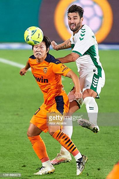Kang-in Lee of Valencia CF competes for the ball with Antonio Barragan of Elche CF during the La Liga Santander match between Elche CF and Valencia...