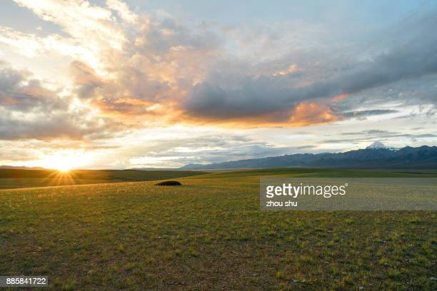 kangrinboqe snowy mountains and  setting sun by the grasslands on the plateau - prairie stock pictures, royalty-free photos & images