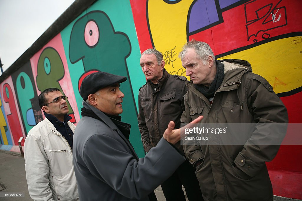 Kani Alavi (2nd from L), Chairman of the East Side Gallery Artists' Association, talks with Arno Paulus (3rd from L), a local real estate development opponent, and Thierry Noir (R), the artist who painted the murals visible behind, while standing next to the East Side Gallery, which is the longest still-standing portion of the former Berlin Wall, close to where a new hotel is scheduled to be built on February 28, 2013 in Berlin, Germany. According to media reports the developer in charge of the project plans to remove an approximately 25-meter long piece of the Wall and transfer it elsewhere in order to allow access to the construction site. Critics, including East Side Gallery mural artists and Spree River embankment development opponents, decry the move, citing the East Side Gallery's status as a protected landmark and a majortourist attraction.