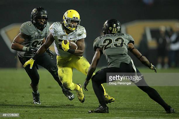 Kani Benoit of the Oregon Ducks carries the ball as Ahkello Witherspoon of the Colorado Buffaloes moves in for the tackle at Folsom Field on October...