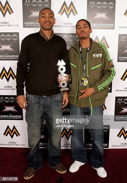 Kano and guest pose backstage in the awards room with Kano's Evening Standard award for Best UK Newcomer at the MOBO Awards 2005, the tenth...