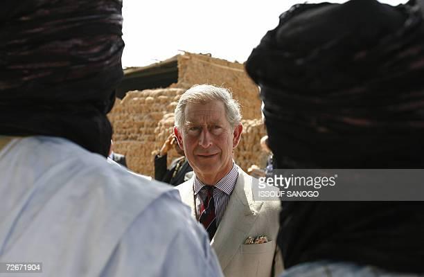 Britain?s Prince Charles looks at two turban clad men in the village of Dawakin Kudu, near Kano, 29 November 2006. Britain?s Prince Charles received...