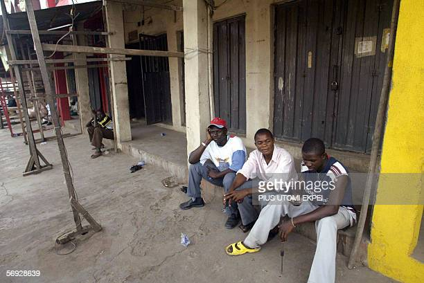 Traders sit in front of their shops closed to business for fear of being looted 24 February 2006 in Kano Business activities were lowkeyed in Kano...