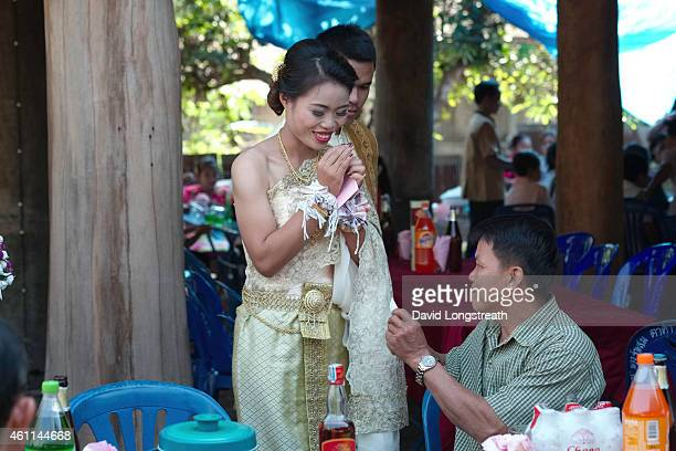 Kanokporn and Montri Thi greet members of the village and accept wedding gifts during ceremonies in Ta Par Mok Thailand Thai Buddhist marriage...
