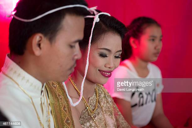 Kanokporn and Montri Thi look on during ceremonies at their wedding in Ta Par Mok Thailand Thai Buddhist marriage ceremonies are generally divided...