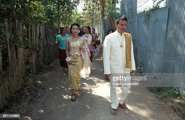 Kanokporn and Montri Thi walk a narrow lane outside their home during wedding ceremonies in Ta Par Mok Thailand Thai Buddhist marriage ceremonies are...