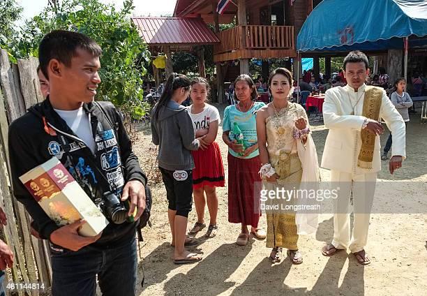 Kanokporn and Montri Thi walk outside their home during wedding ceremonies in Ta Par Mok Thailand Thai Buddhist marriage ceremonies are generally...