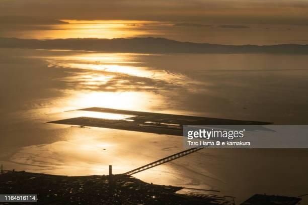 kansai international airport and osaka bay in japan sunset time aerial view from airplane - internationaler flughafen kansai stock-fotos und bilder