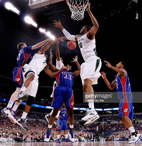 Kansas' Brady Morningstar left Mario Little middle and Marcus Morris battle the Michigan State defenders for a rebound during the opening half in the...