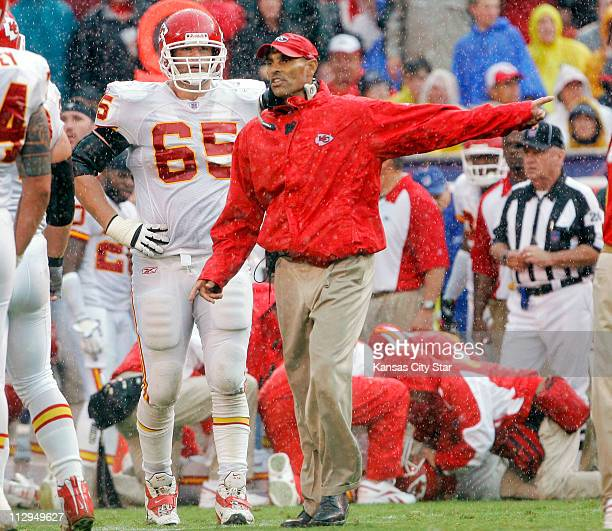 Kansas City Chiefs coach Herm Edwards center motions for his team to get to the sidelines as medical staff look after Chiefs quarterback Trent Green...