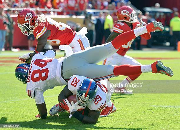 Kansas City Chiefs defensive back Husain Abdullah forces New York Giants tight end Larry Donnell into running back Michael Cox in the closing minutes...
