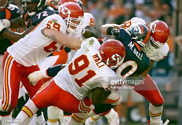 Kansas City Chiefs defensive end Jared Allen left Tamba Hali lower center and linebacker Kawika Mitchell stuff Denver Broncos running back Mike Bell...