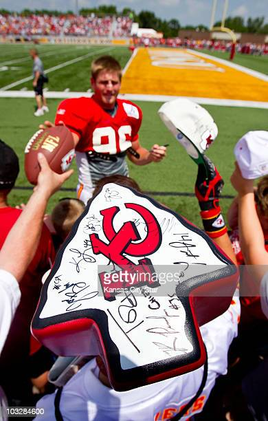Kansas City Chiefs fan Travis Stucky of Sabetha, Kansas, wore a Chiefs foam head while looking for autographs from linebacker Andy Studebaker, top,...