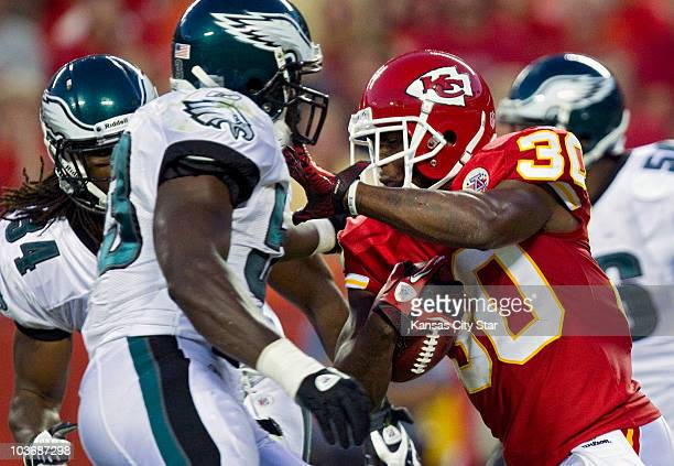 Kansas City Chiefs kick returner Javier Arenas tries to drive past Philadelphia Eagles' Moise Fokou on a punt return in the second quarter at...
