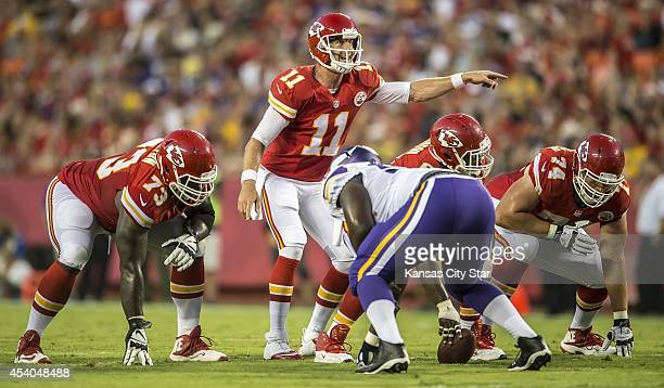 Kansas City Chiefs quarterback Alex Smith motions for adjustments with guards Zach Fulton and Jeffrey Linkenbach against the Minnesota Vikings in...