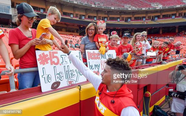 Kansas City Chiefs quarterback Patrick Mahomes exchanges fist-bumps with fansbefore a preseason football game against the Houston Texans on Thursday,...